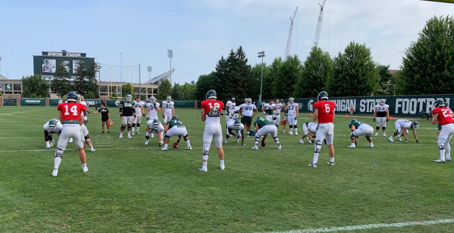 MSU quarterbacks warm up with offensive linemen early at Mondays practice. (Credit: Eric Bach / WDBM)