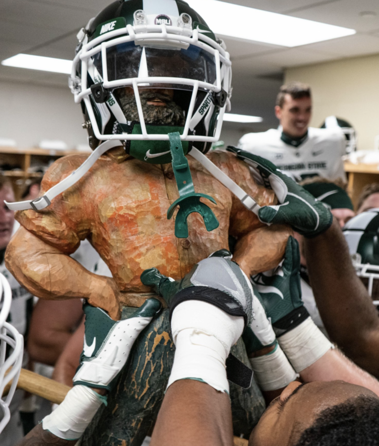 MSU celebrates beating Michigan by lifting the Paul Bunyan trophy/ Photo Credit: MSU Athletic Communications