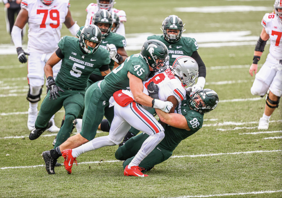 Noah+Harvey+%2845%29+and+Jacub+Panasiuk+%2896%29+and+others+combine+for+a+tackle+on+OSU+RB+Trey+Sermon%2F+Photo+Credit%3A+MSU+Athletic+Communications%0A%0A