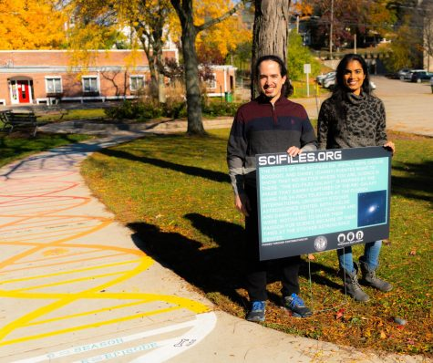 Chelsie and Daniel at Valley Court Park. They are holding the sign with the description of their artwork and they are standing by the Rainbow DNA art