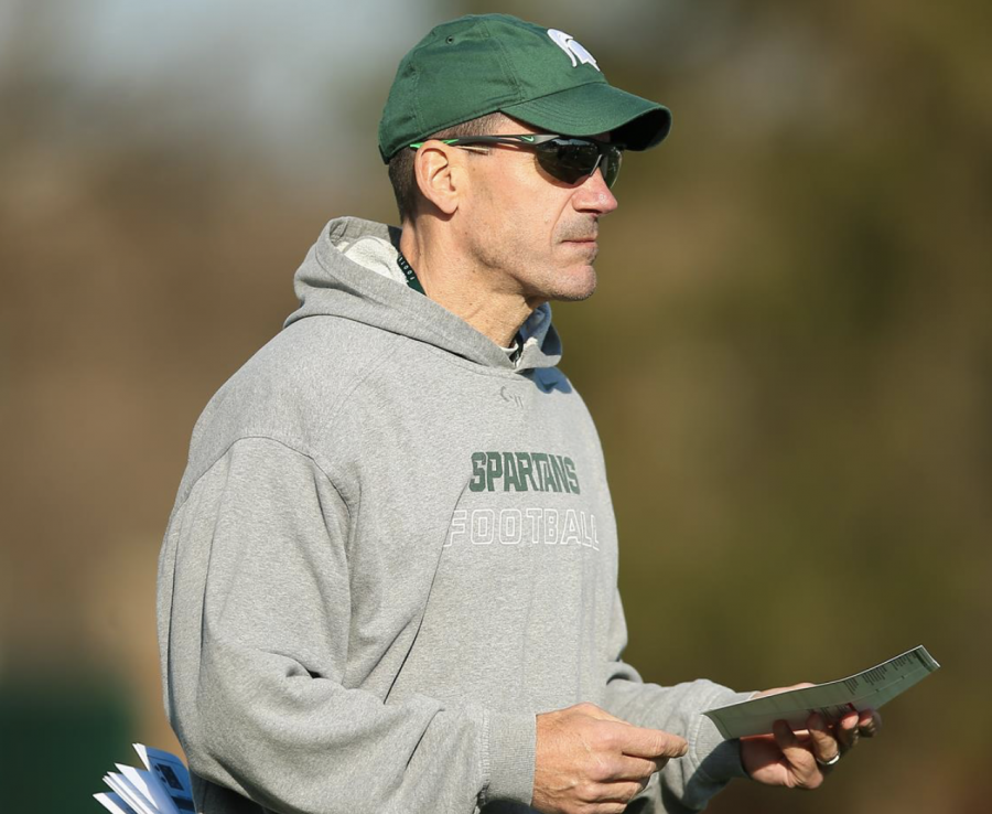 Former MSU offensive coordinator Dave Warner looks over a play-calling sheet/ Photo Credit: MSU Athletic Communications