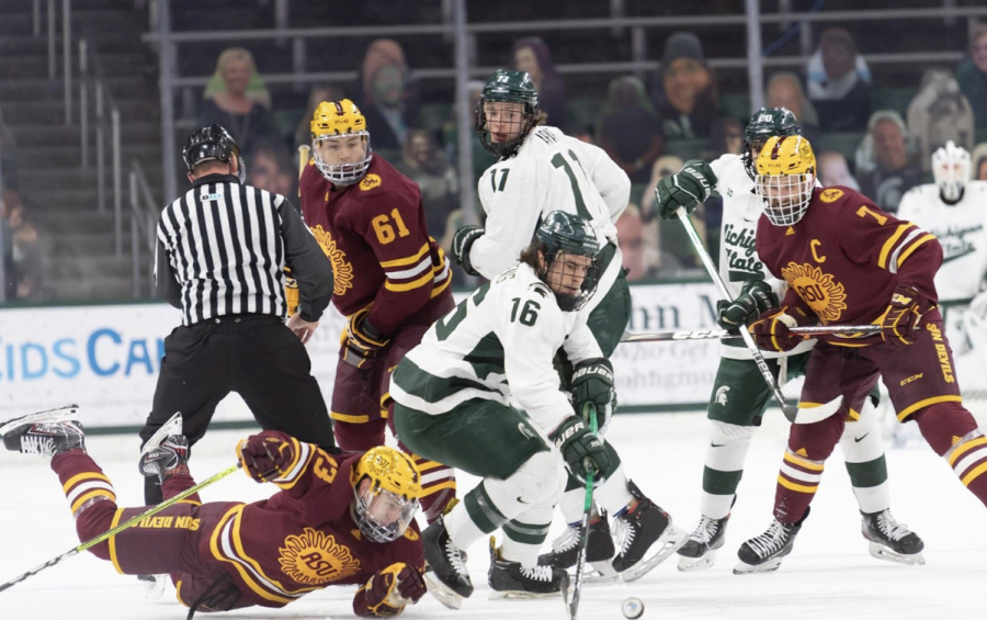 MSU forward Brody Stevens (16) dives for the puck amidst a sea of Arizona State players/ Photo Credit: MSU Athletic Communications