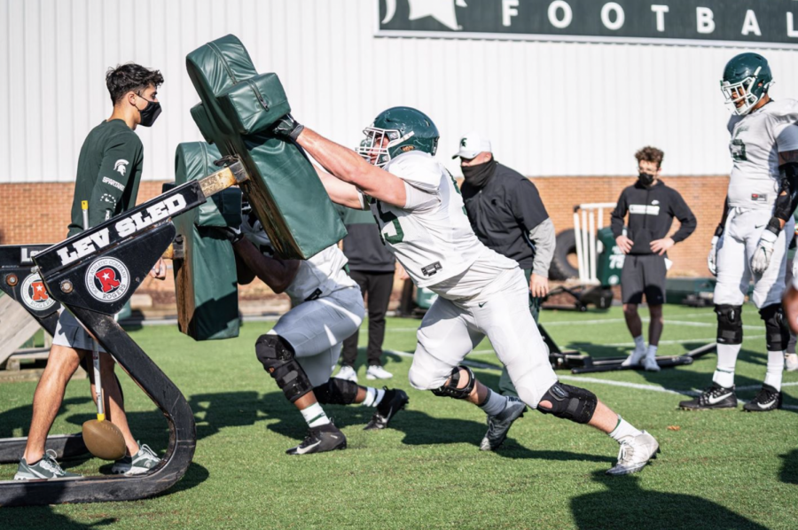 MSU offensive line coach Chris Kapilovic supervises a sled-driving drill during 2021 spring practice/ Photo Credit: MSU Athletic Communications