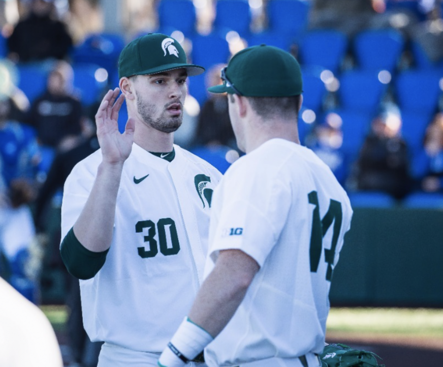 MSU pitcher Mason Erla high-fives teammate Andrew Morrow/ Photo Credit: MSU Athletic Communications