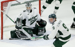 MSU goaltender Drew DeRidder glances at a flying puck during a game in 2020/ Photo Credit: MSU Athletic Communications