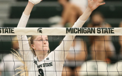 MSU middle blocker Emma Monks (9) guards the front of the net during a game in 2021/ Photo Credit: MSU Athletic Communications