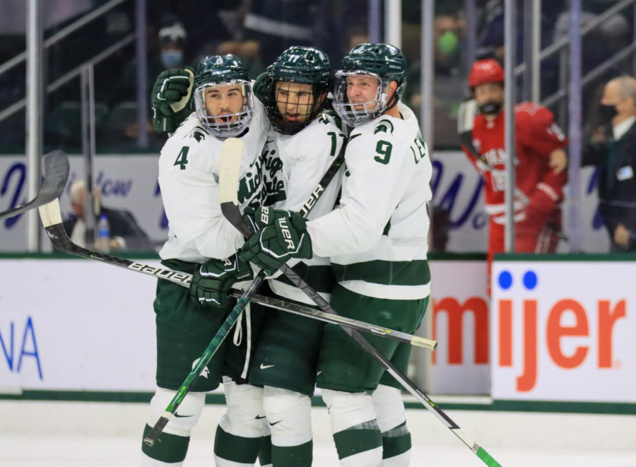 MSU forward Jeremy Davidson (11) gets congratulated by defenseman Nash Nienhius (4) and forward Mitchell Lewandowski (9) after scoring a goal in the Spartans 3-1 win over Miami (OH) on Oct. 15, 2021/ Photo Credit: Sarah Smith/WDBM